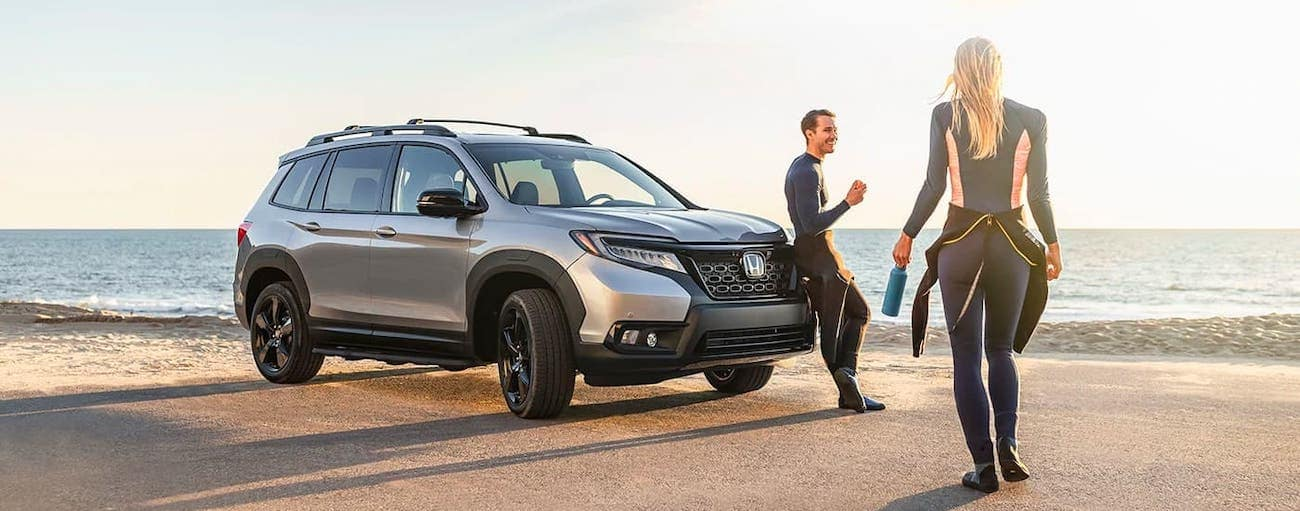 Two people in wetsuits are approaching their silver 2020 Honda Passport AWD Elite at a beach.
