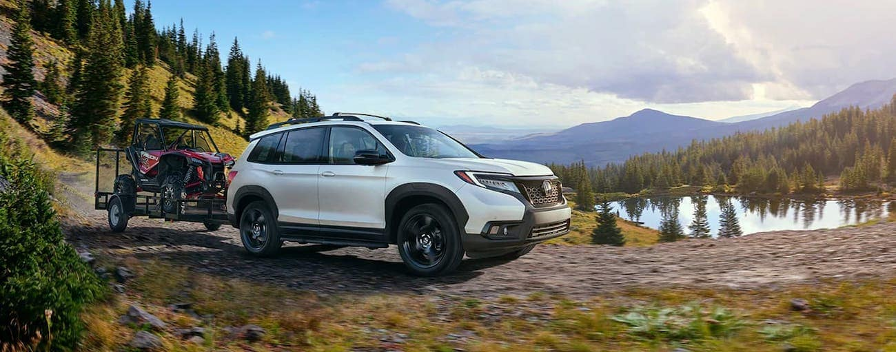 A white 2020 Honda Passport AWD Elite is towing a trailer and Side by Side in front of a lake and mountains.