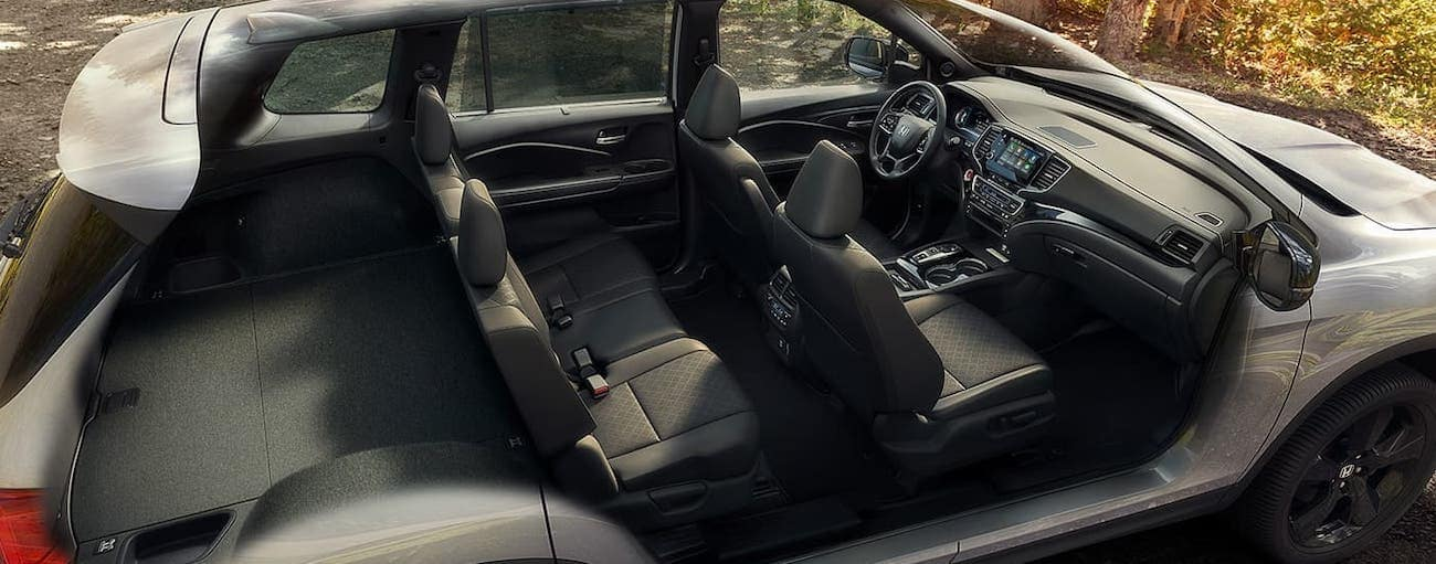 A cross section is shown of a silver 2020 Honda Passport Elite near Rochester, NY, showing the black interior.