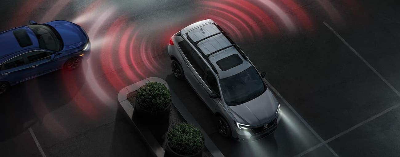 A silver 2020 Honda Passport Elite is shown from above backing out of a parking spot in Rochester, NY, with simulated Traffic Monitoring.