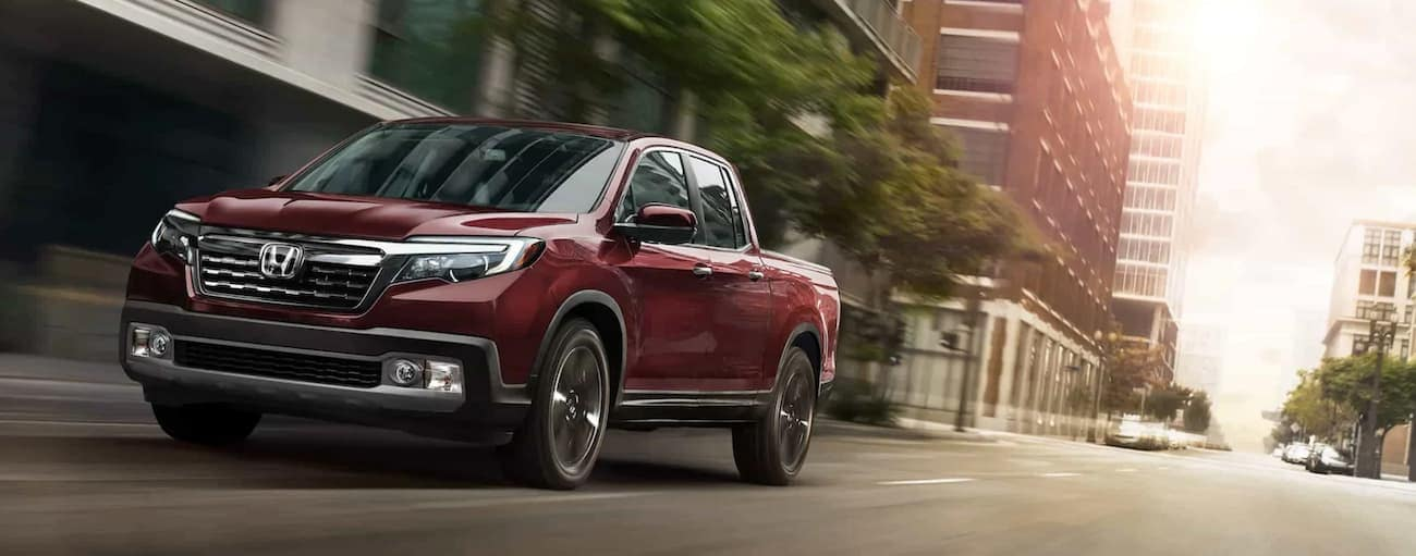 A red 2020 Honda Ridgeline RTL-E is driving down a Rochester, NY street.