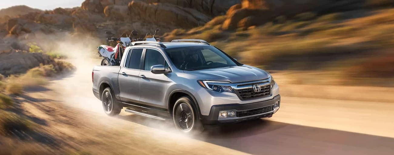 A silver 2020 Honda Ridgeline AWD RTL-E is driving on a dirt road with dirt bikes in the bed.