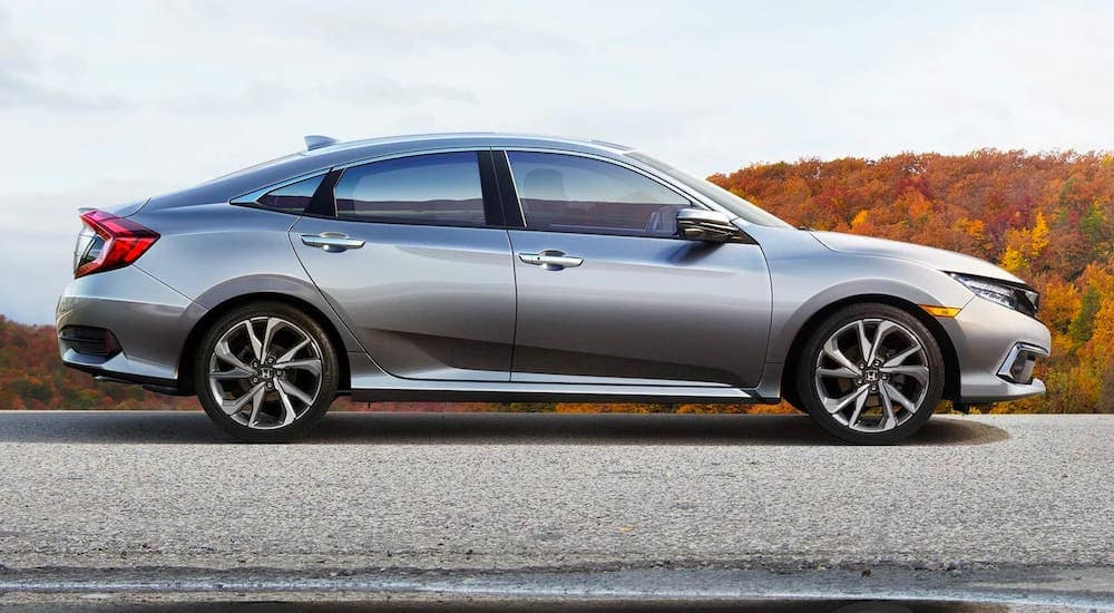 A silver 2019 Honda Civic Sedan Touring is parked on a road in fall.