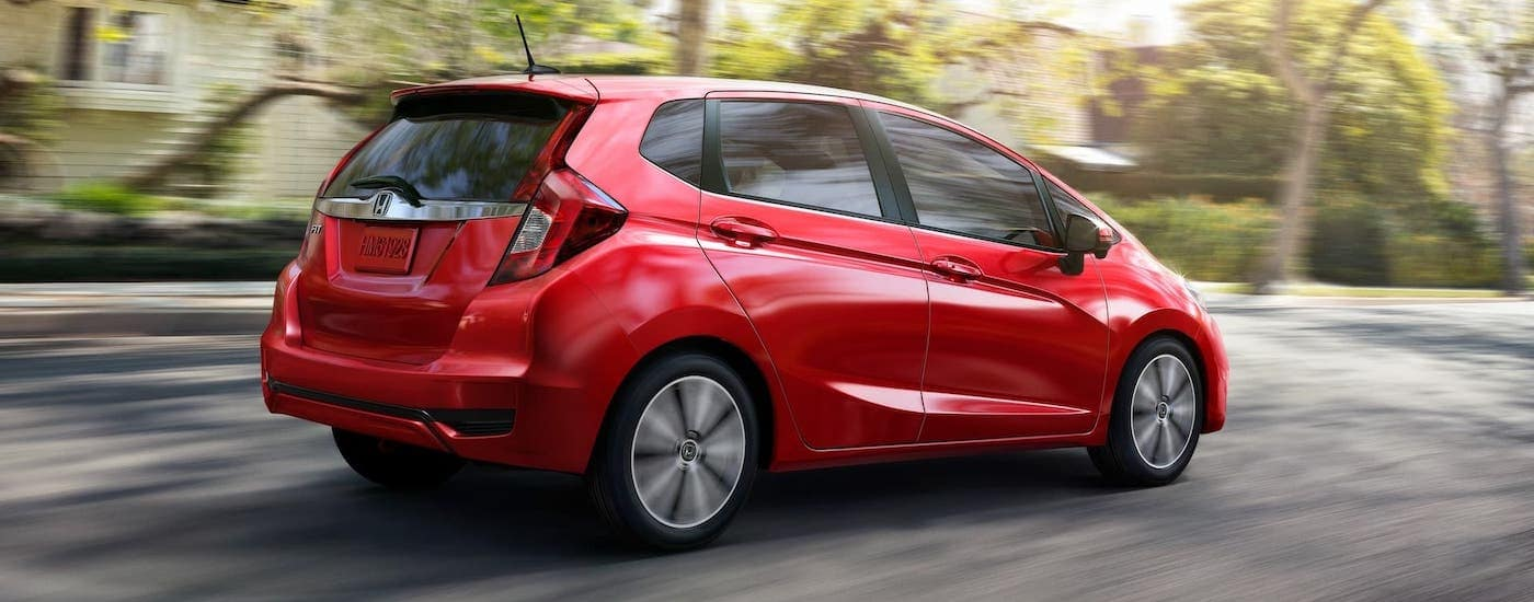 A red 2020 Honda Fit EX-L from a Honda dealer near me is driving down a tree-lined roadl.