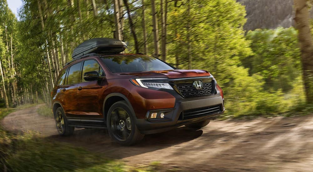 A red 2020 Honda Passport is driving on a dirt road near Rochester, NY.