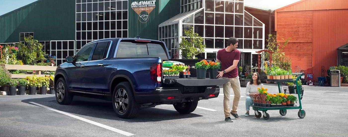 A couple is loading plants into the bed of a blue 2020 Honda Ridgeline RTL-E in front of a garden center near Rochester, NY.
