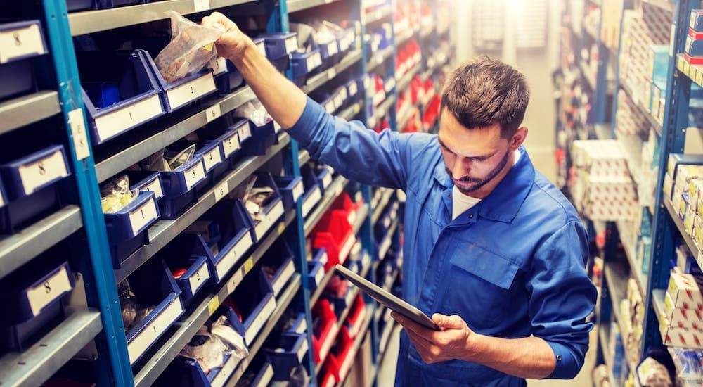 A mechanic in a blue jump suit is in a warehouse picking out OEM parts.