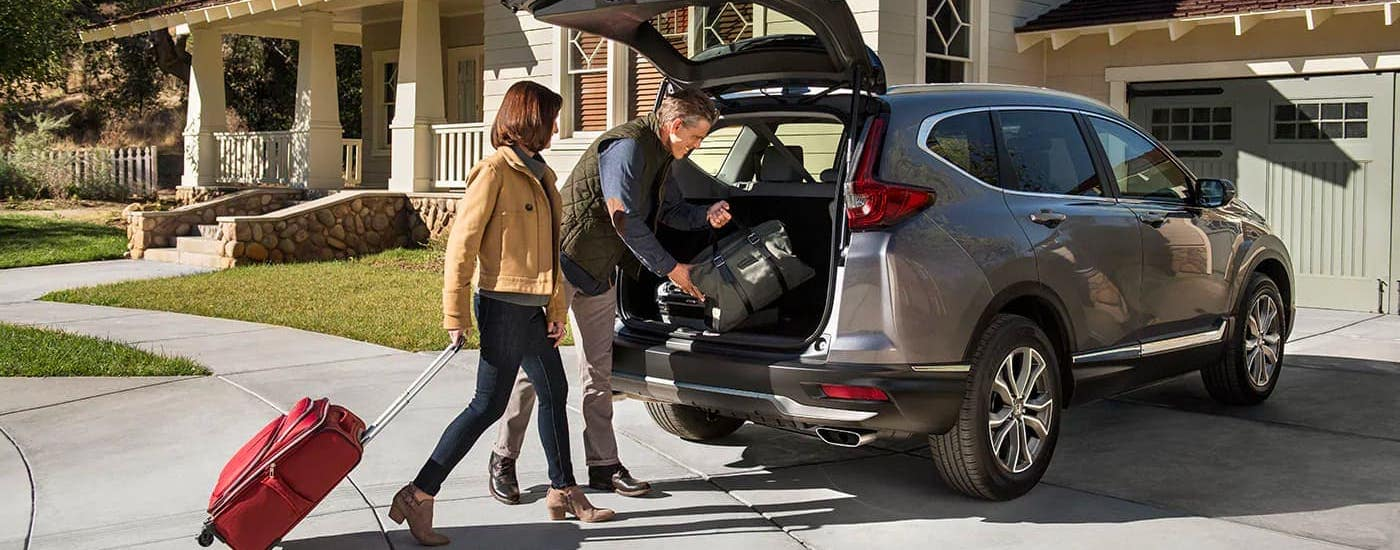A couple is loading cargo into the rear of their Honda CR-V Touring since it won the 2020 Honda CR-V vs 2020 Ford Escape comparison.