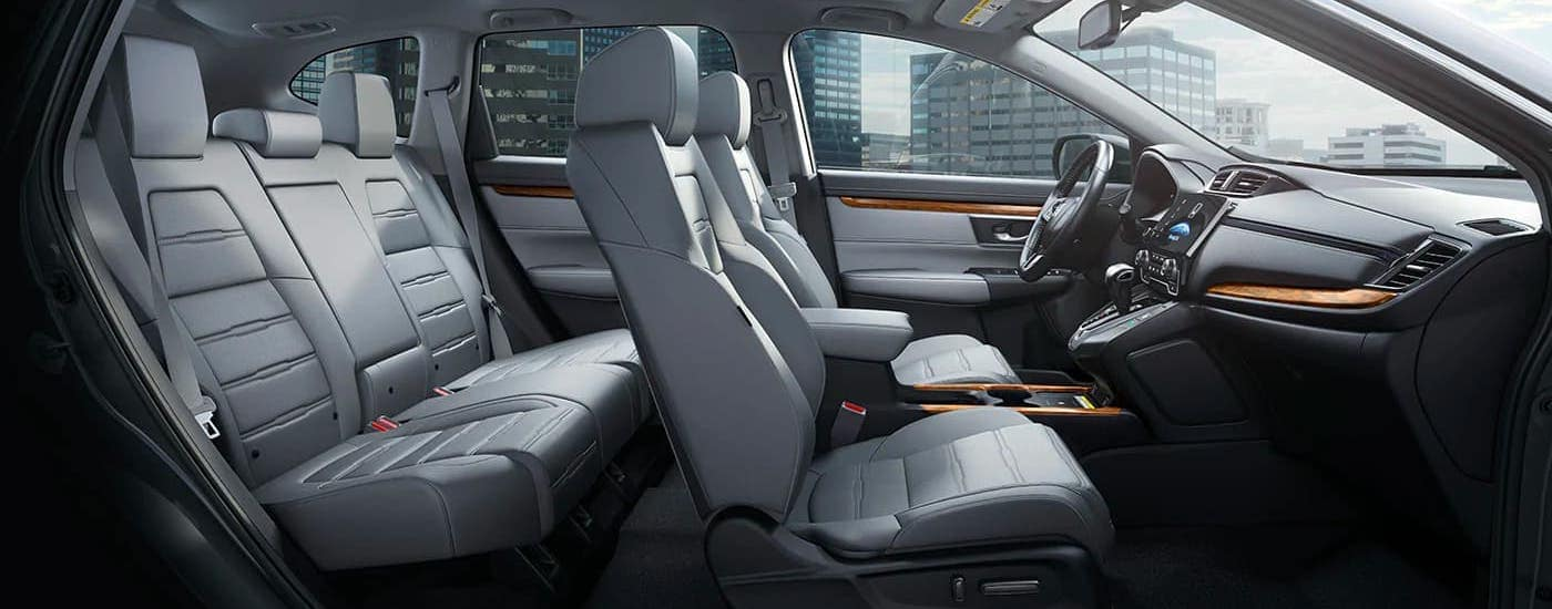 The gray leather interior of a 2020 Honda CR-V Touring is shown with a city seen through the windows.