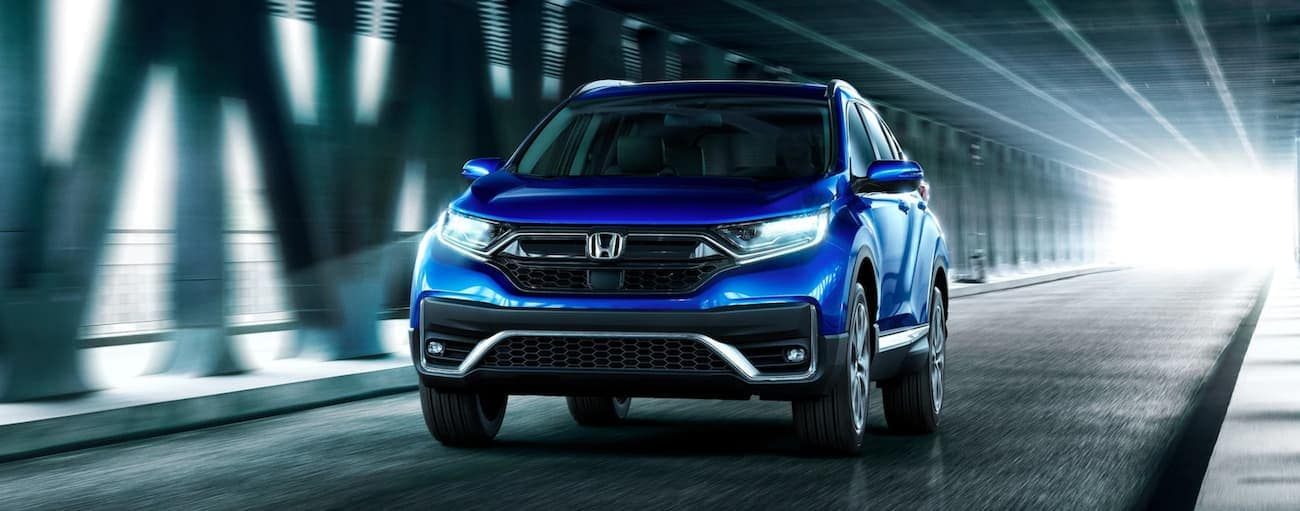 A blue 2020 Honda CR-V Touring is driving on a covered city bridge near Rochester, NY, at night.