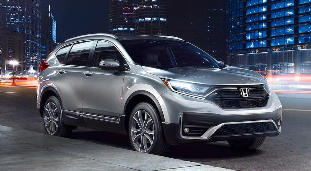 A silver 2020 Honda CR-V Touring from a local Honda dealer is parked on a city street at night.