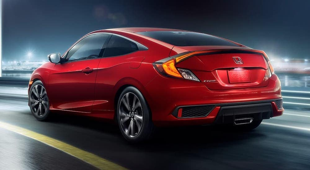 A red 2020 Honda Civic Coupe Sport is driving on a city street at night, facing away.