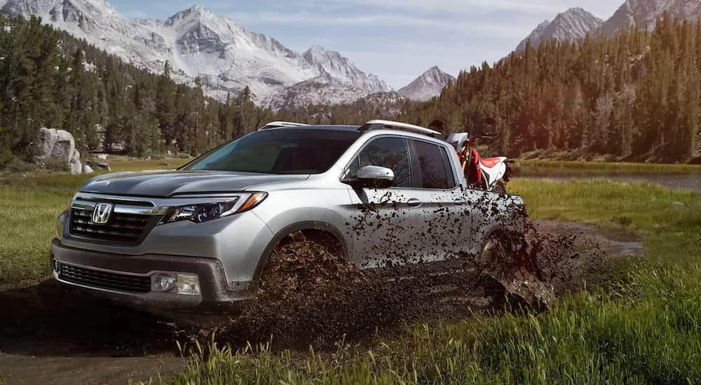 A silver 2020 Honda Ridgeline RTL-E is off-roading in the mud with a dirt bike in the bed and mountains in the distance.