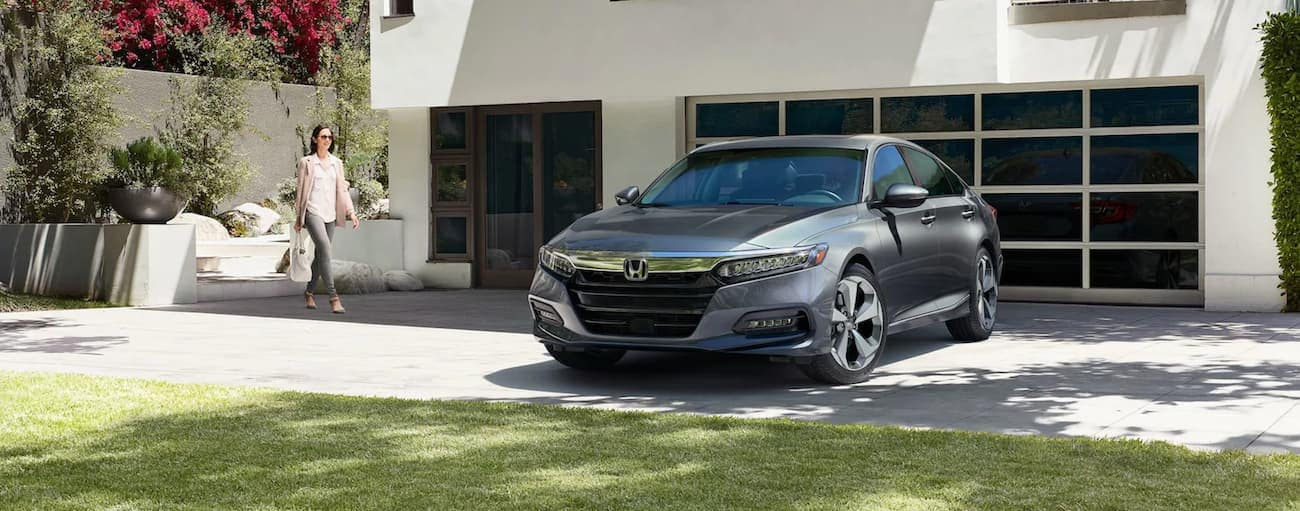 A grey 2020 Honda Accord Touring 2.0T is parked in front of a modern white home after winning the 2020 Honda Accord vs 2020 Toyota Camry comparison.