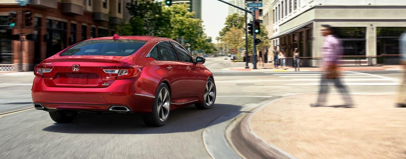 A red 2020 Honda Accord Touring 2.0T is driving around a corner on a city street near Rochester, NY.