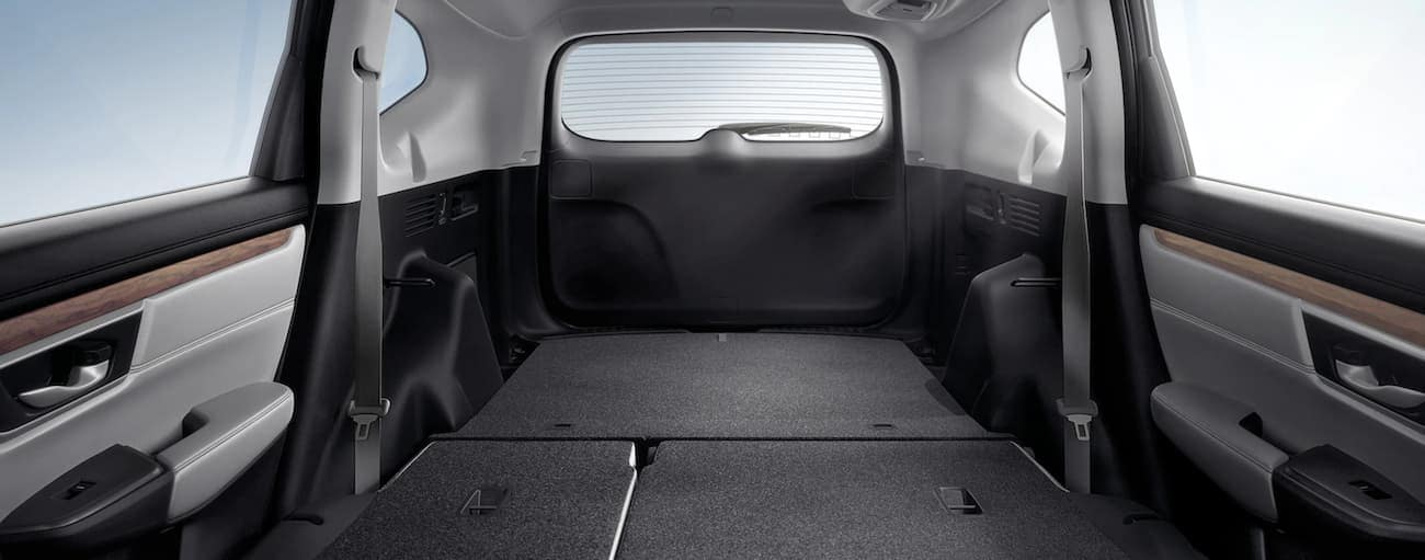 The cargo area of a 2020 Honda CR-V Touring is shown with the seats down.
