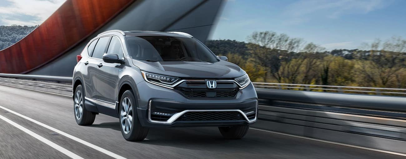 A grey 2020 Honda CR-V Hybrid Touring is driving past a modern bridge near Rochester, NY.