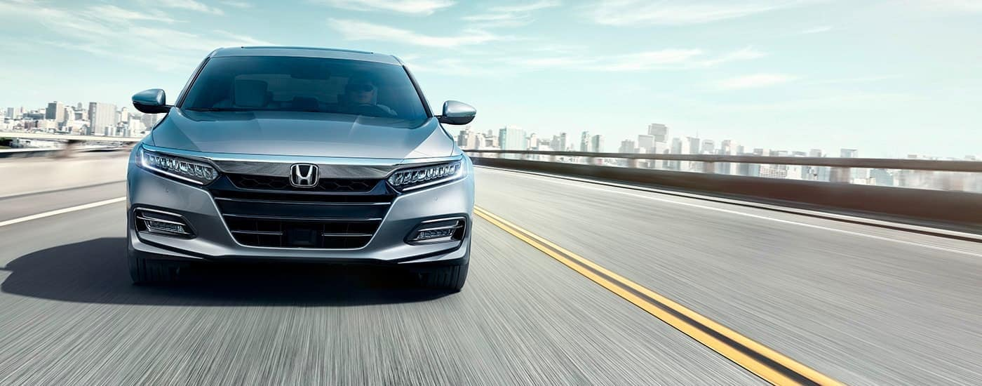 A silver 2020 Honda Accord is shown from the front driving away from a city after winning the 2020 Honda Accord vs 2020 Kia Optima comparison.