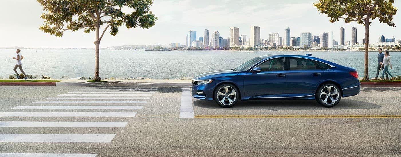 A blue 2020 Honda Accord is shown from the side with a river and city in the distance.