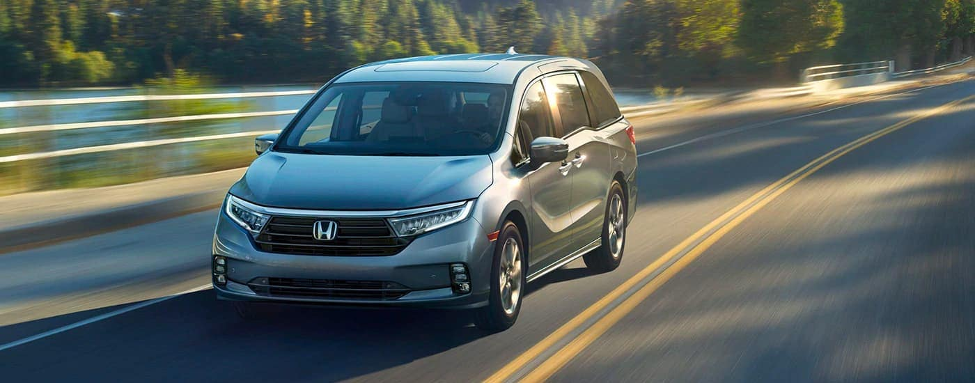 A gray 2020 Honda Odyssey Elite is driving on a rural highway near Rochester, NY.