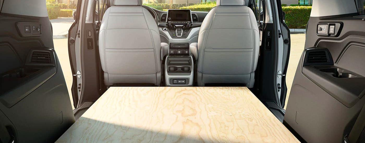 A sheet of plywood is shown in the back seat of a 2020 Honda Odyssey Touring.