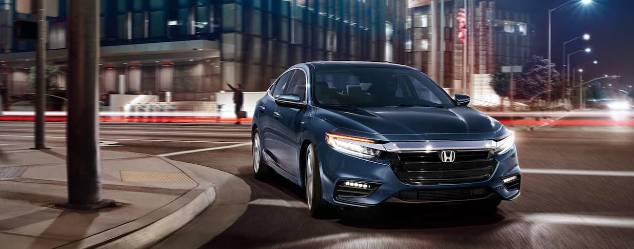 A dark blue 2021 Honda Insight Touring is driving around a corner in a city at night.