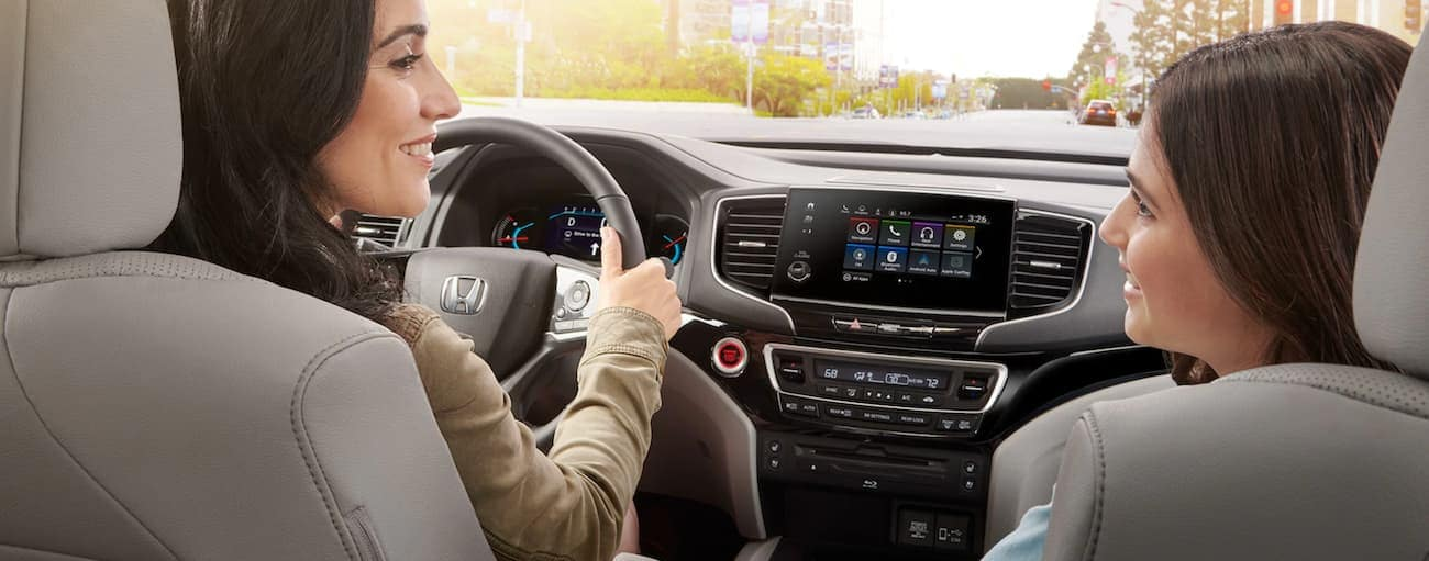 A mother and daughter are in the front seats of a 2021 Honda Pilot Elite.