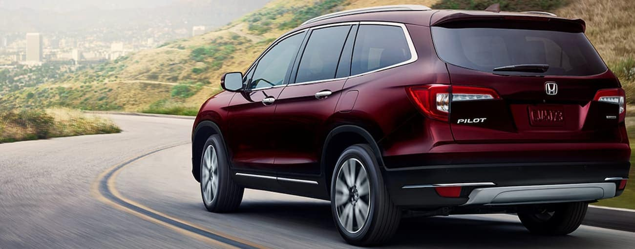 A dark red 2012 Honda Pilot Touring is driving down hill on a winding road.