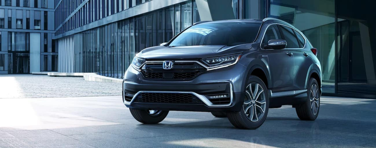 A dark grey 2020 Honda CR-V Hybrid Touring is parked in front of an office building after wining the 2020 Honda CR-V vs 2020 Chevy Equinox comparison.