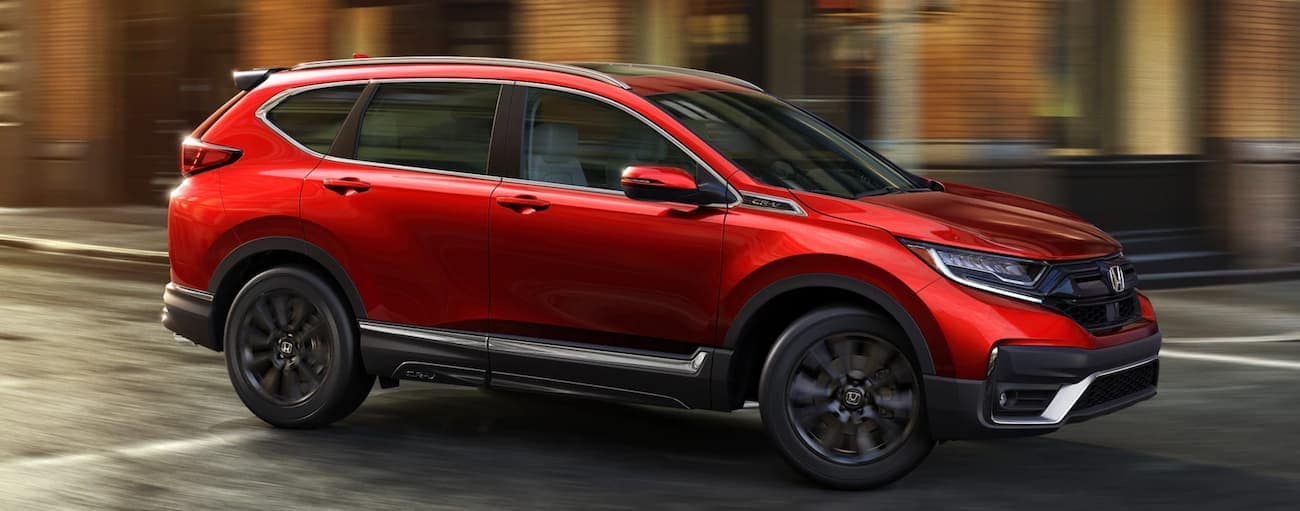 A red 2020 Honda CR-V Touring is driving past a brick building near Rochester, NY.
