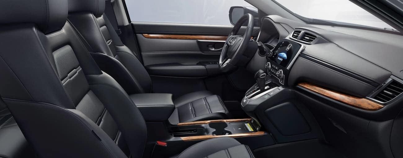 The black and woodgrain interior in a 2020 Honda CR-V Touring is shown from the side.