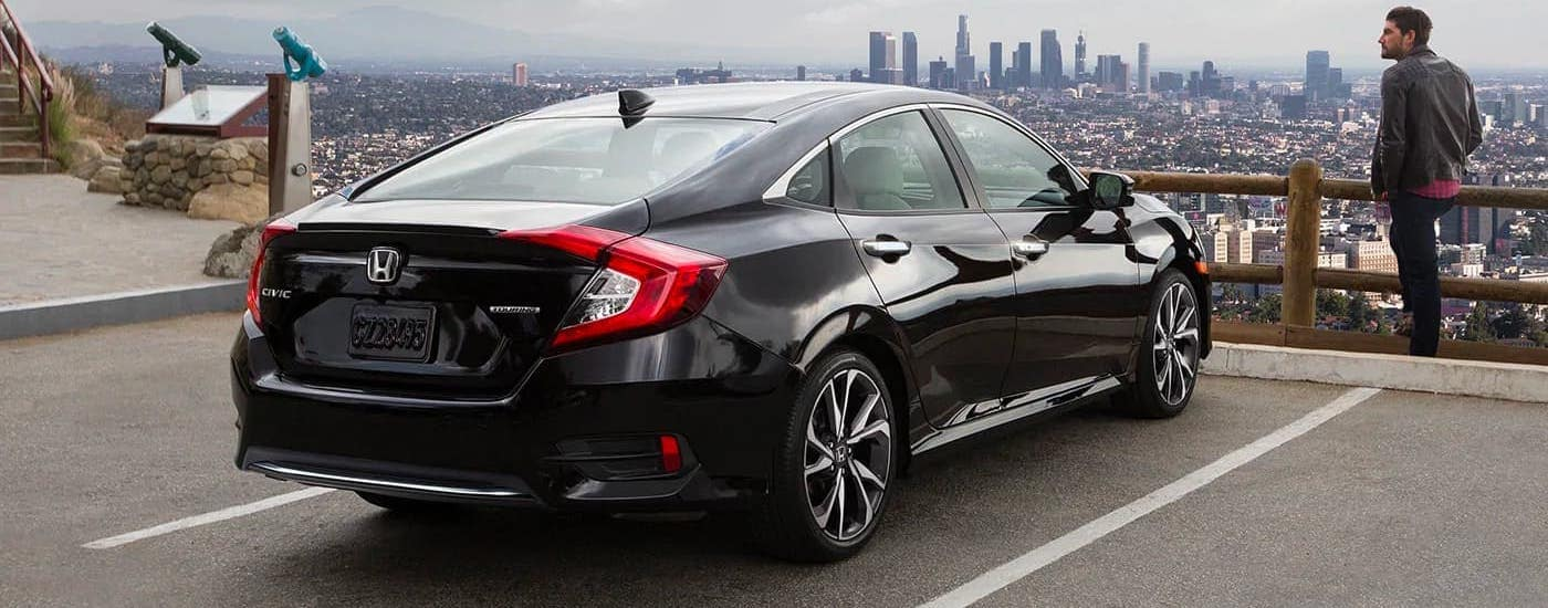 A black 2021 Honda Civic is parked on a hill overlooking a distant city.