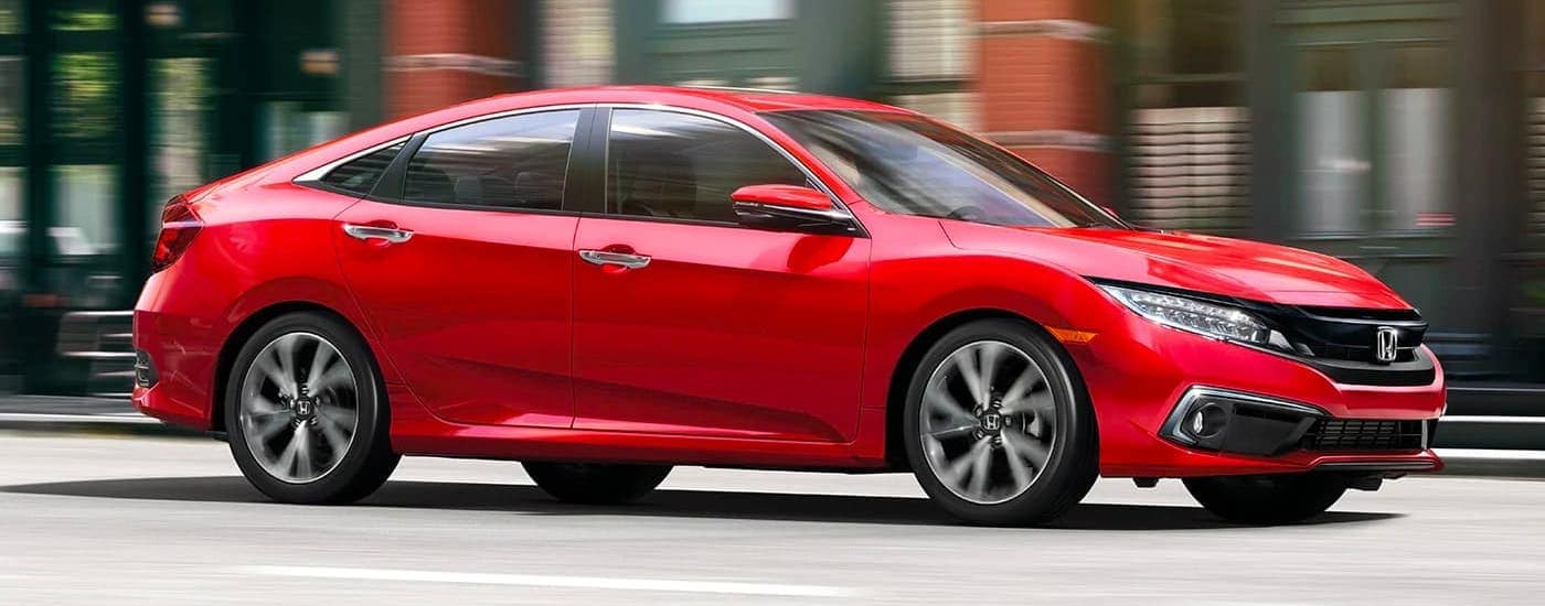 A red 2021 Honda Civic Touring is driving on a city street and shown from the side.