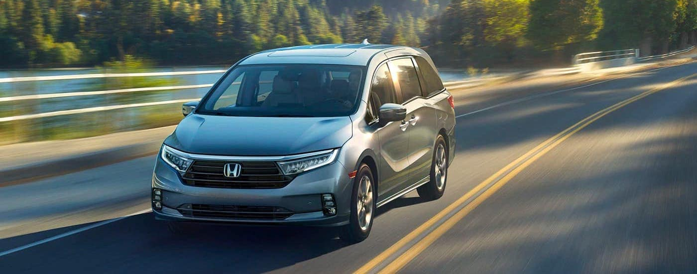 A green 2021 Honda Odyssey Elite is shown driving on a highway from the front.