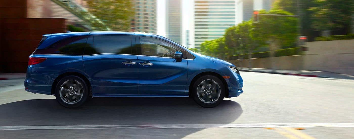 A blue 2021 Honda Odyssey Elite is driving on a city street and shown from the side.