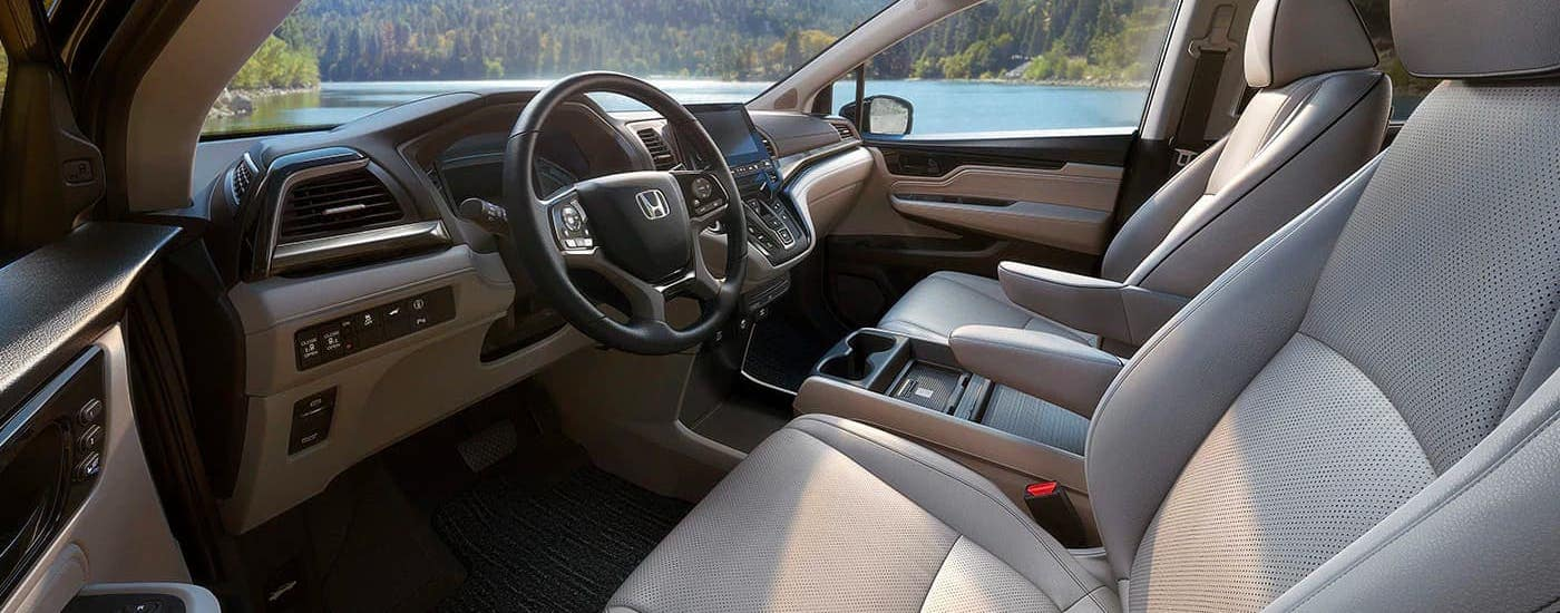The front seats in a 2021 Honda Odyssey Elite are shown from the driver's side.