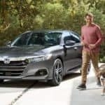 A popular Honda Car, a grey 2021 Honda Accord Hybrid is parked in a driveway with a man walking his dog.