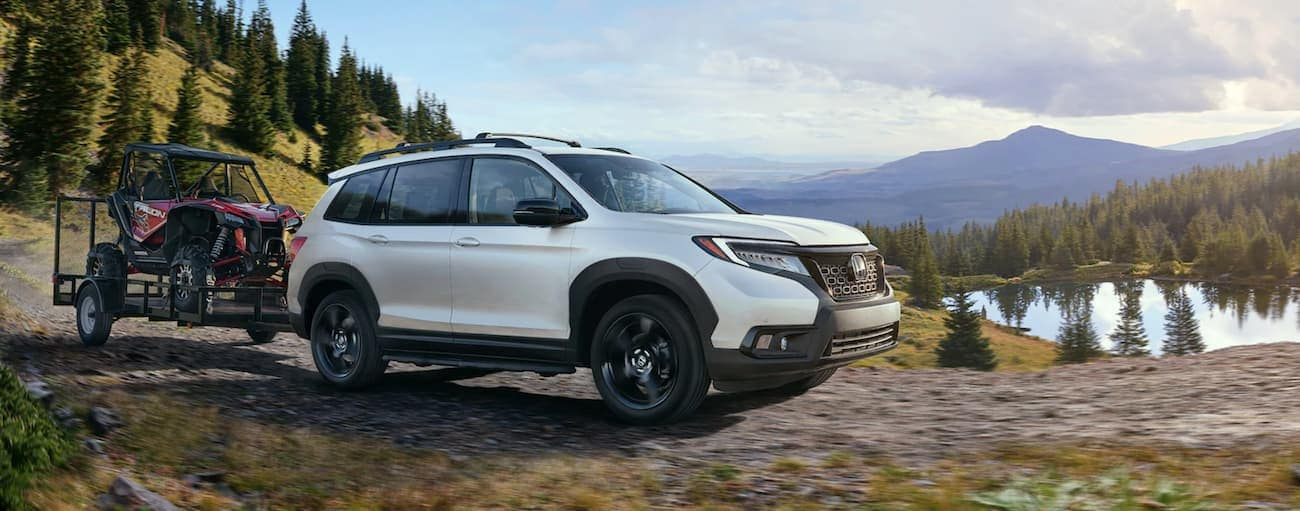 A white 2021 Honda Passport Elite is towing a side-by-side past a lake on a dirt road.
