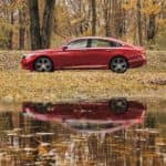 A red 2021 Honda Accord Hybrid is parked in the woods near a lake after leaving Honda dealer near Brockport.