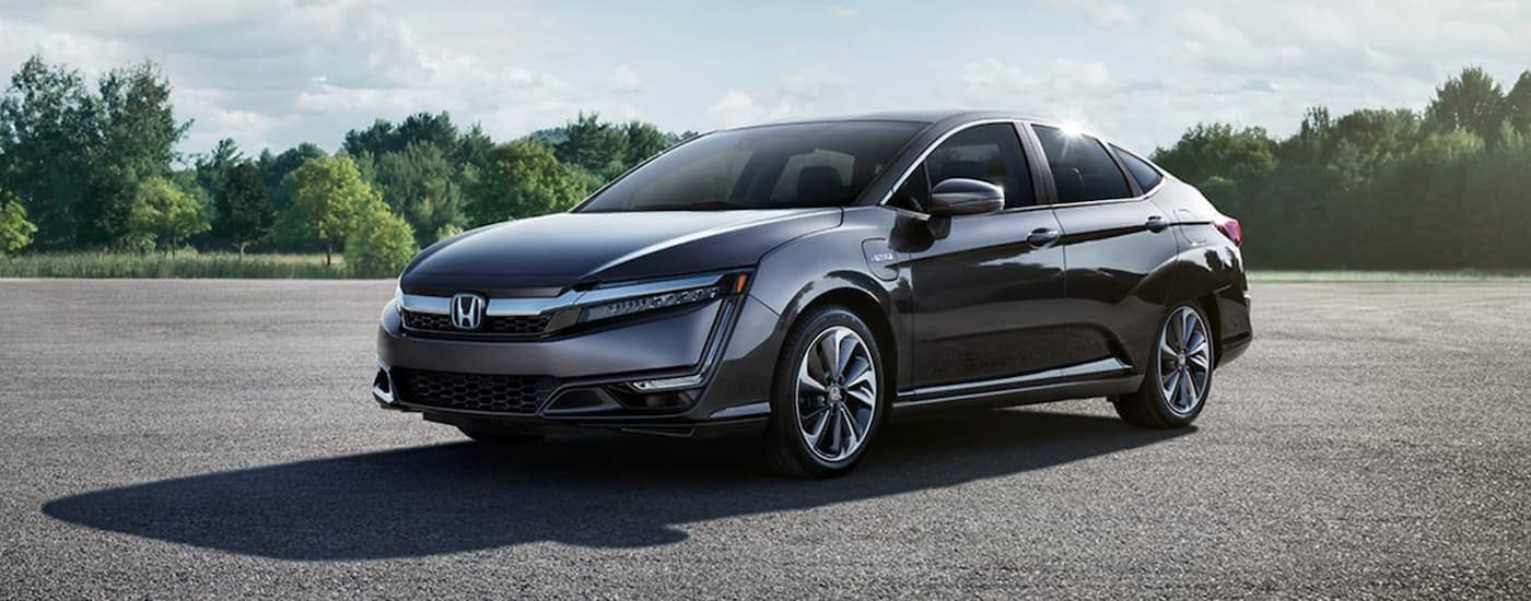 A grey 2021 Honda Clarity Plug-In from a Honda dealer in Rochester is parked in an open parking lot.