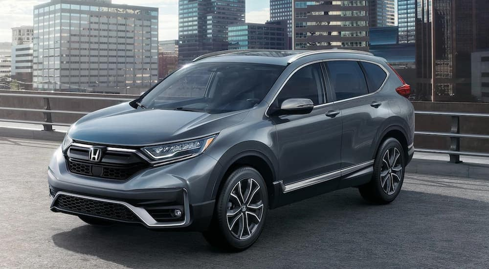 A grey 2021 Honda CR-V Touring is parked on a rooftop parking area in a city.