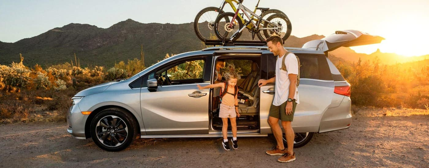 A dad is helping his daughter out of a silver 2021 Honda Odyssey Elite with bikes on the roof.