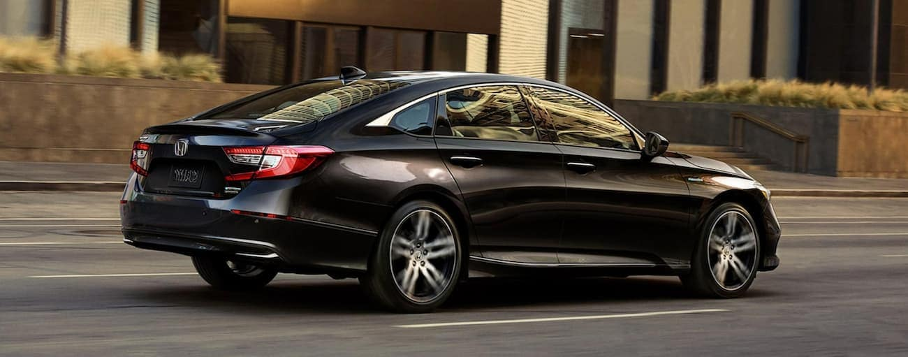 A black 2021 Honda Accord Hybrid is driving on a city street after winning the 2021 Honda Accord vs 2021 Kia K5 comparison.
