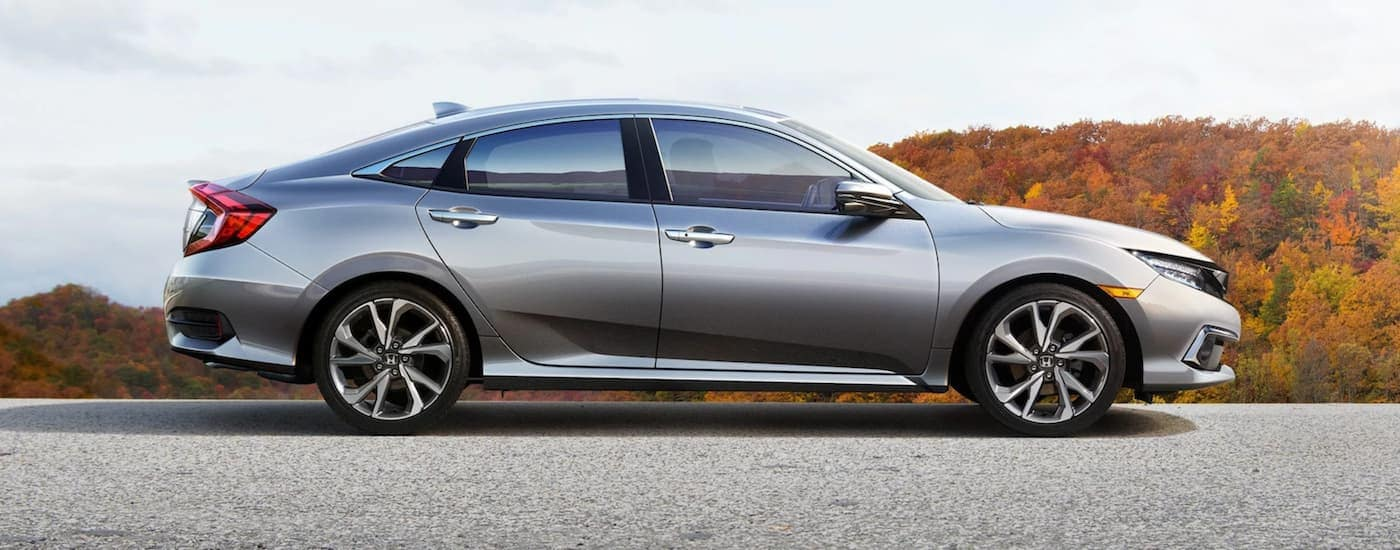 A silver 2021 Honda Civic is shown from the side with trees during autumn in the background.