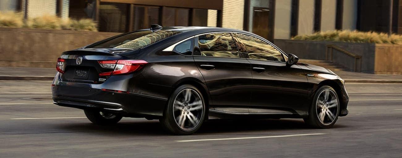 A black 2021 Honda Accord Hybrid is driving on a city street.