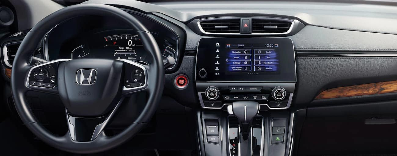 The wheel and infotainment screen are shown in a 2021 Honda CR-V Touring.