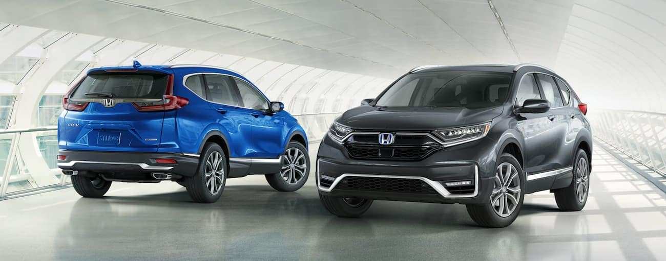 A blue 2021 Honda CR-V Touring and a grey 2021 Honda CR-V Hybrid are parked in a bright parking garage.