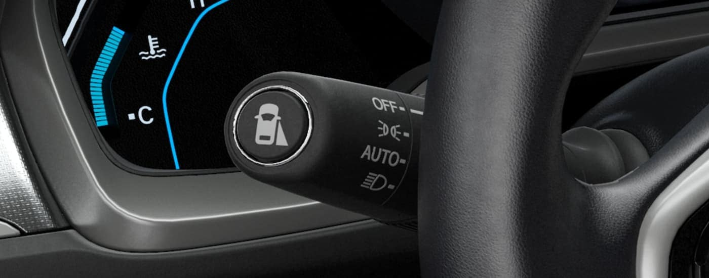 A close up shows the lane keep assist icon on the black headlight stalk in a 2021 Honda Civic EX.