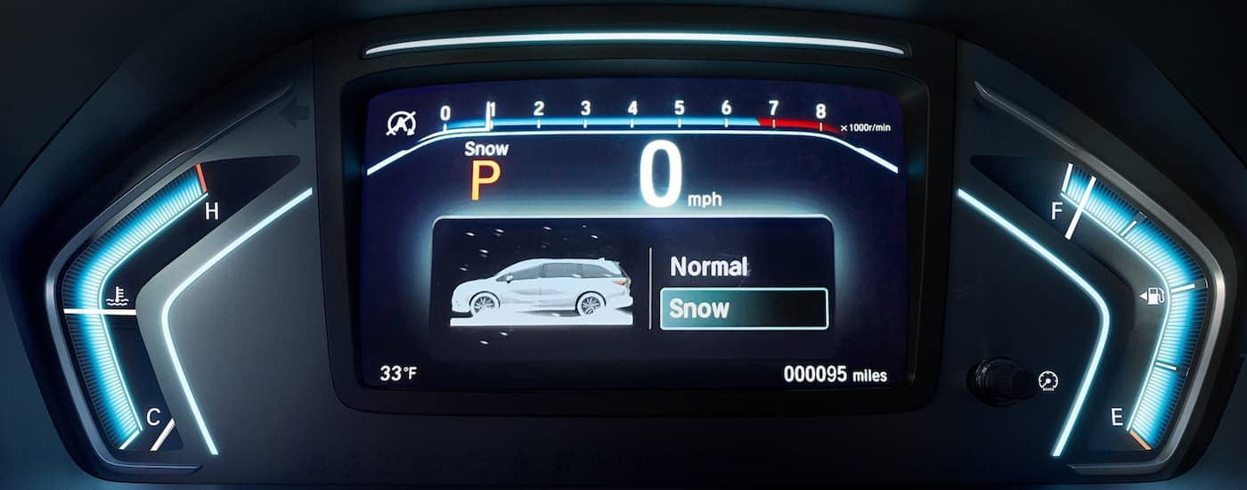 A close up shows gauge cluster and traction selection mode in a 2022 Honda Odyssey.
