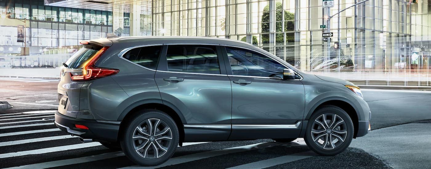 A pale blue 2021 Honda CR-V is shown driving through the city at night.
